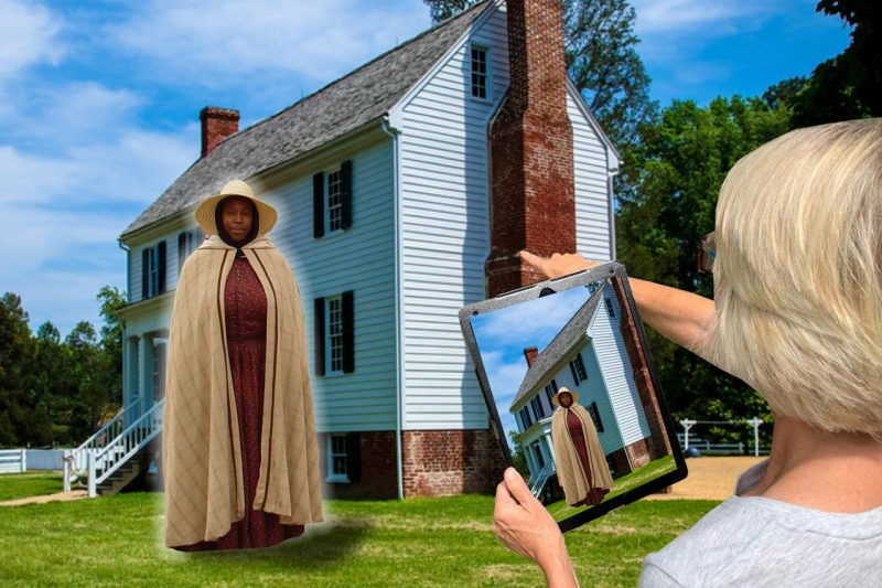 A woman looks at a digital tablet and sees a Civil War era woman standing in front of a historic house