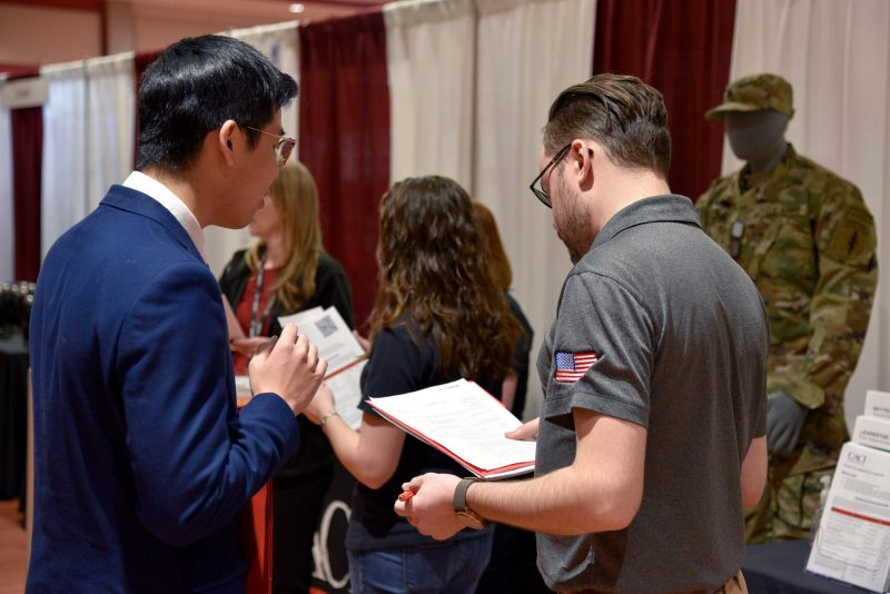 A representative of CACI's university programs team talks with Virginia Tech computer science students at the CS|Source spring 2020 career fair in February, prior to the COVID-19 pandemic.